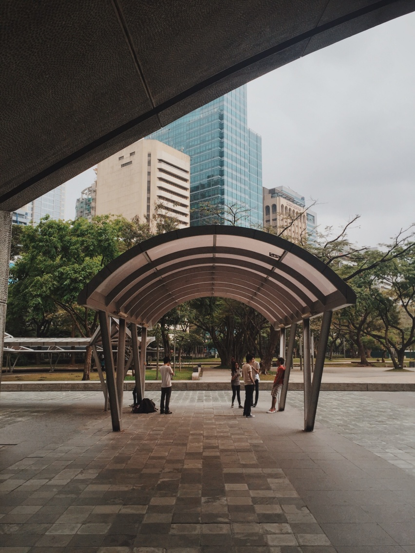 Photo of a group of teenagers under a sunshade in Ayala Triangle, Makati City