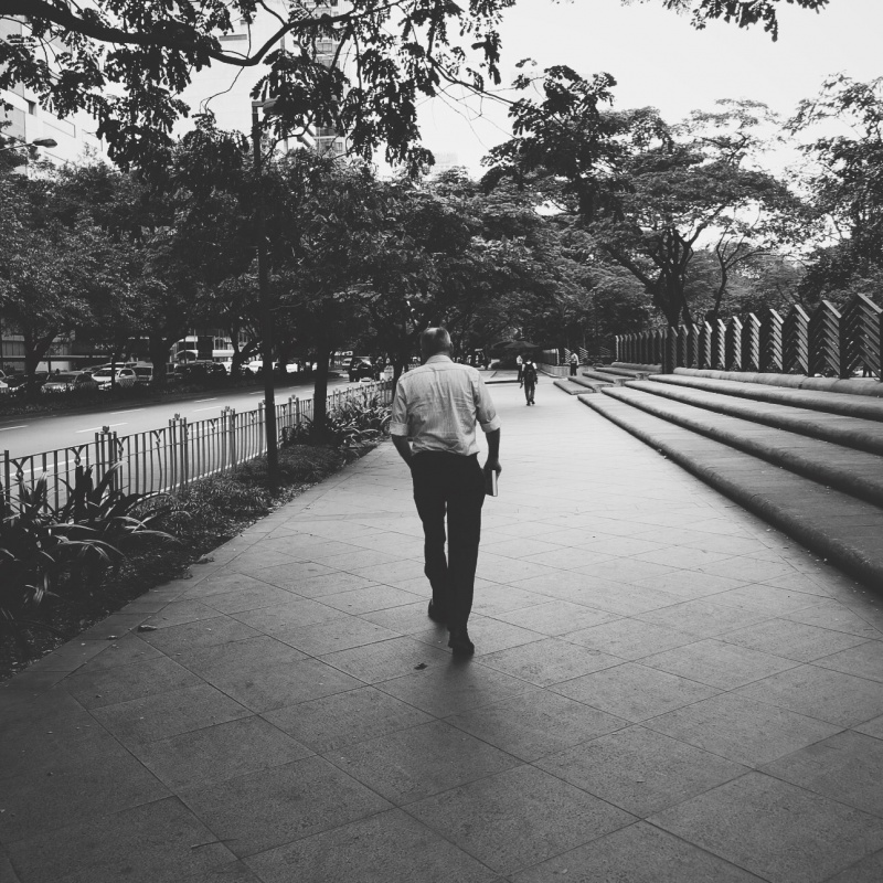 Photo of a man from behind, walking down Paseo De Roxas St. in Makati City
